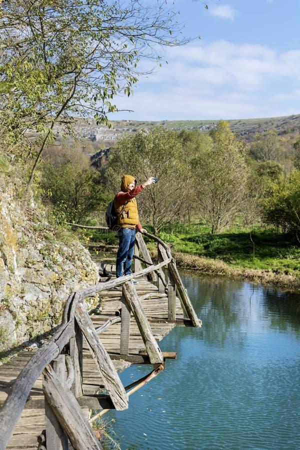 站立在拍与电话的山的一个木桥的旅游人照片 免版税库存图片