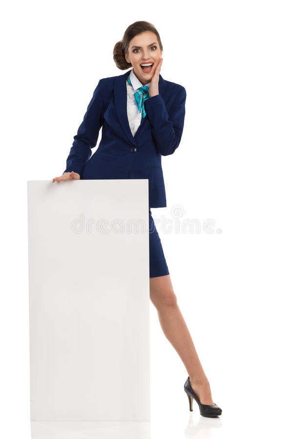站立在招贴后的激动的女实业家 免版税库存照片