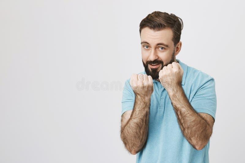 站立在拳击手姿势的激动的成人有胡子的人画象,停滞他的拳头,准备战斗,在灰色背景 免版税库存照片