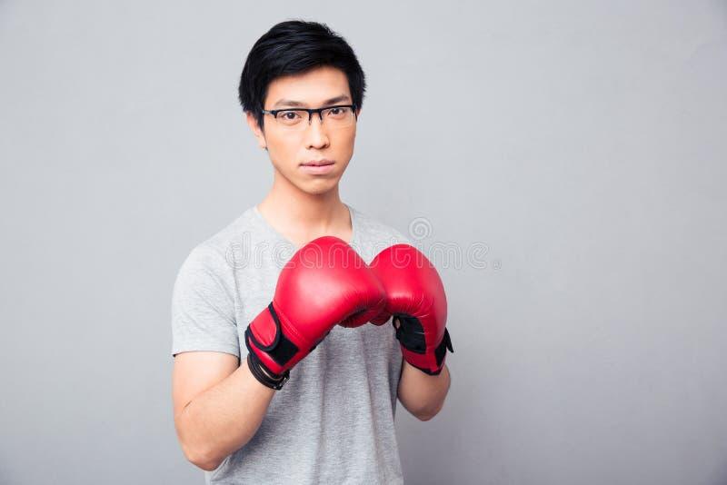 站立在拳击手套的年轻亚裔人 免版税图库摄影