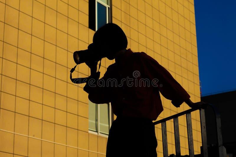站立在拿着照相机的空中女孩 免版税库存图片