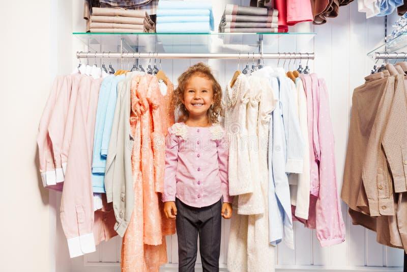 站立在挂衣架的衣裳之间的逗人喜爱的小女孩 免版税库存照片