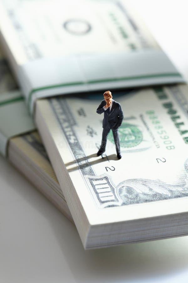 站立在捆绑100的经理小雕象美元笔记 免版税库存图片