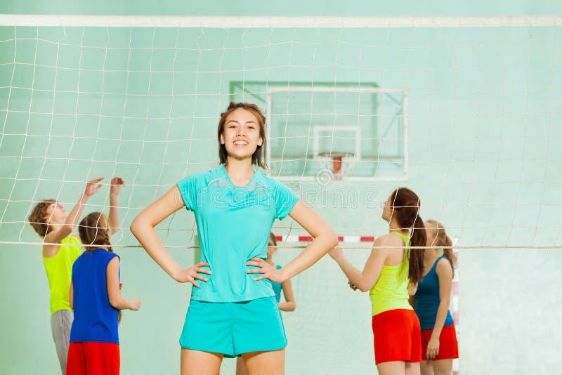 站立在排球网旁边的亚裔十几岁的女孩 免版税库存图片