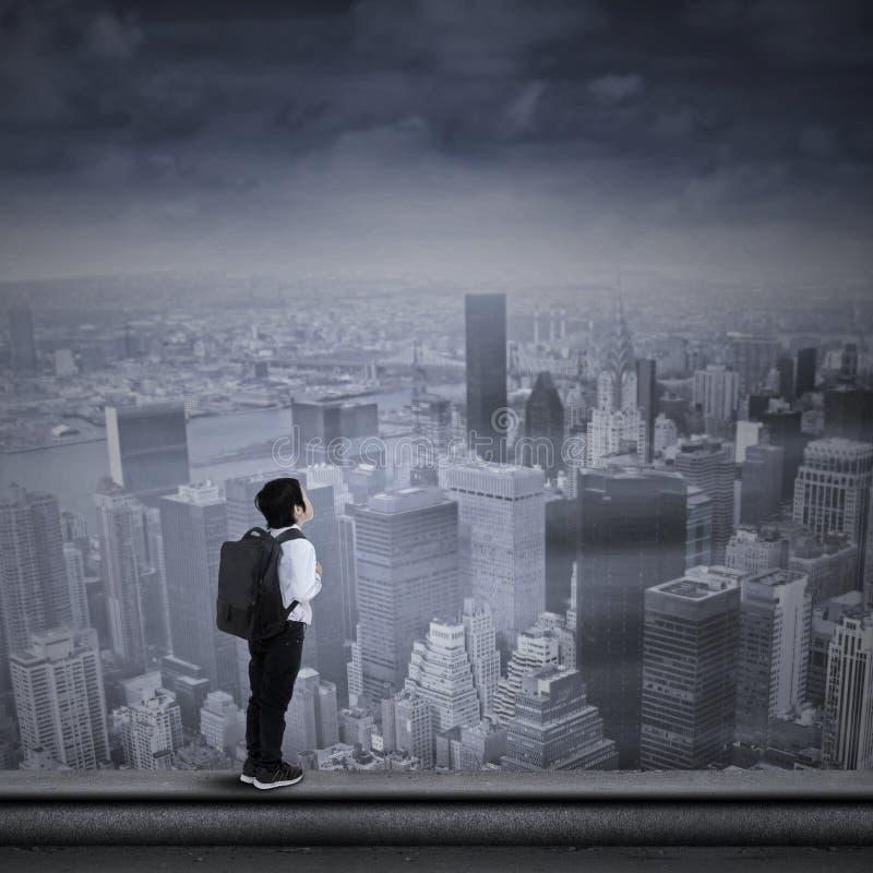 站立在摩天大楼上面的年轻商人  免版税图库摄影