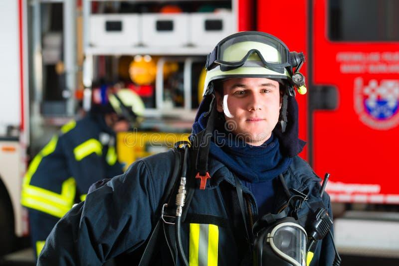 制服的年轻消防员在救火车前面 免版税库存照片