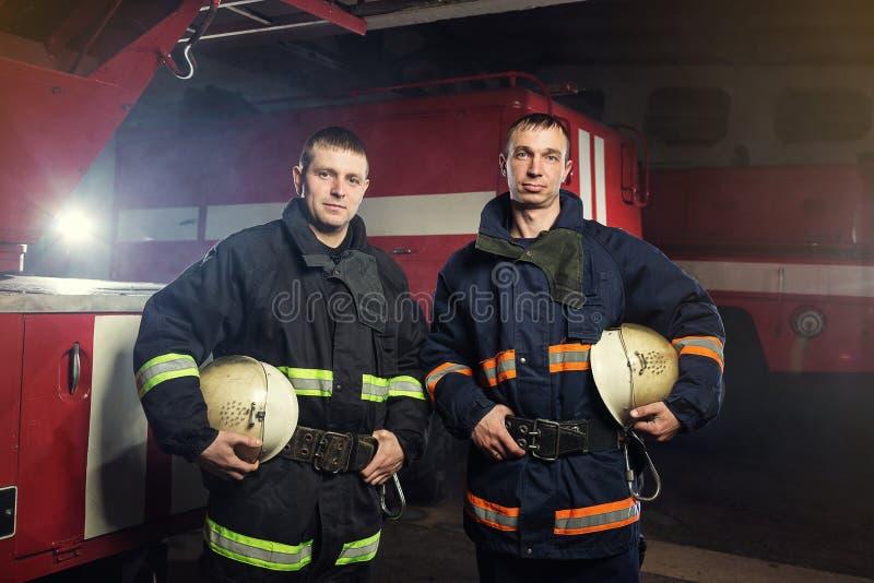 站立在救火车附近的行动的消防员消防队员 Eme 免版税库存照片
