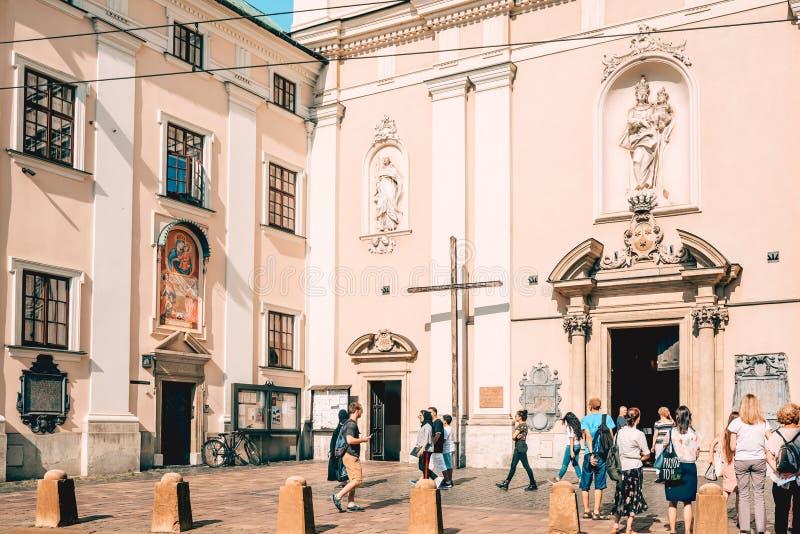 站立在教会前面的人在老镇克拉科夫,波兰 免版税库存照片