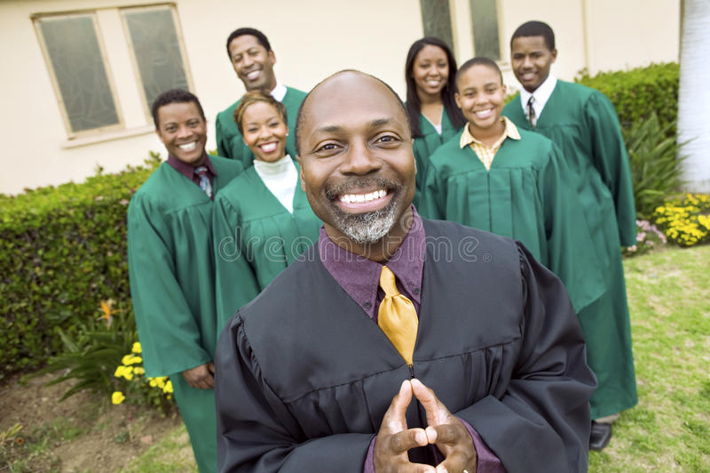 站立在教会前面的传教者和唱诗班 库存图片