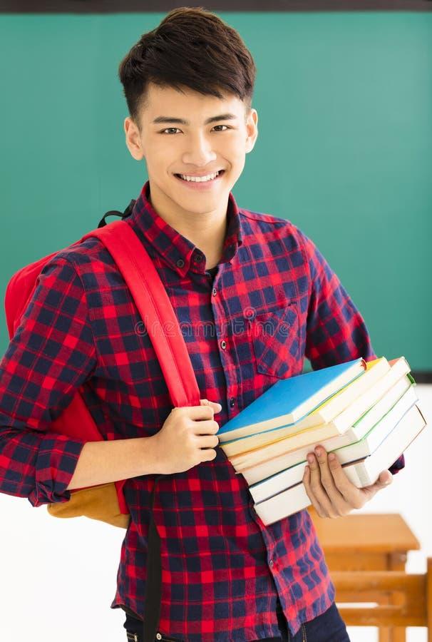 站立在教室的微笑的男学生 免版税库存照片