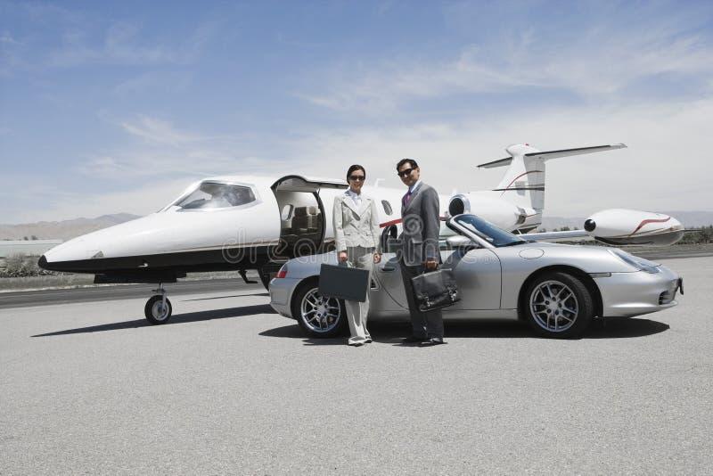 站立在敞篷车和私人喷气式飞机前面的企业夫妇 免版税库存照片