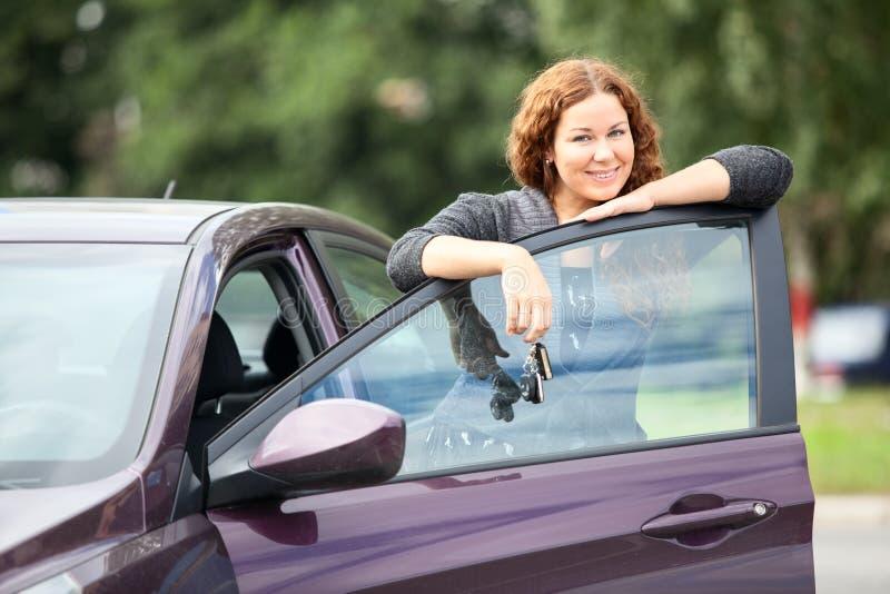 站立在新的汽车附近的笑的愉快的妇女 免版税库存照片