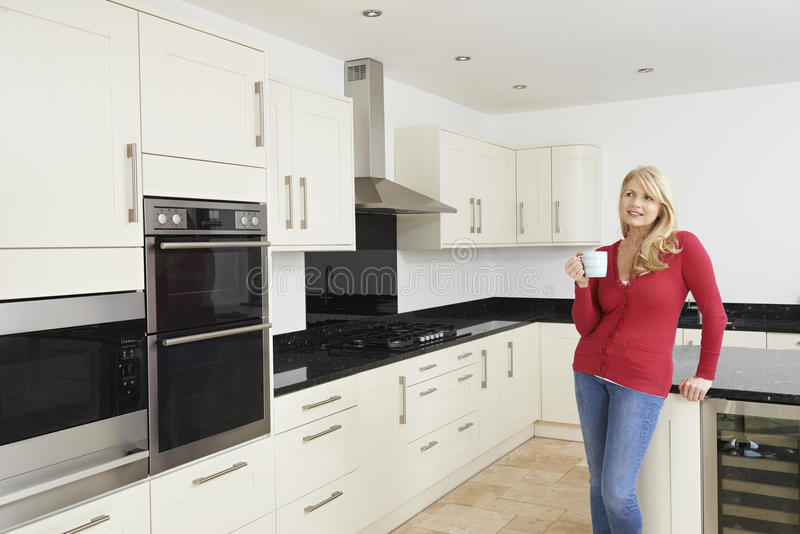 站立在新的豪华适合的厨房里的成熟妇女 库存图片