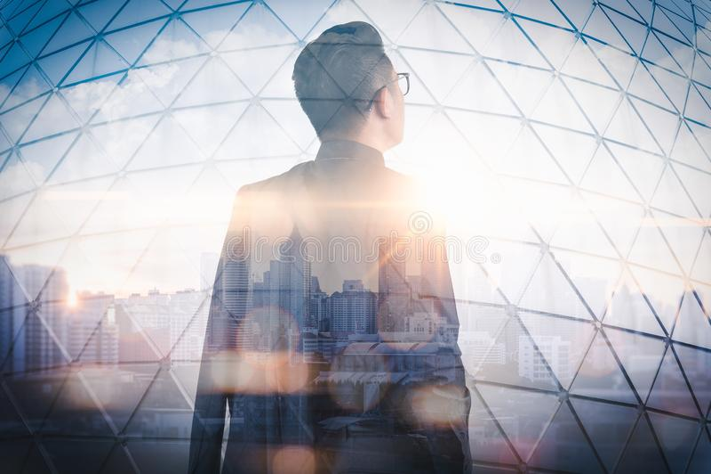 站立在日出期间的商人的两次曝光图象躺在与都市风景图象 现代生活的概念 库存图片