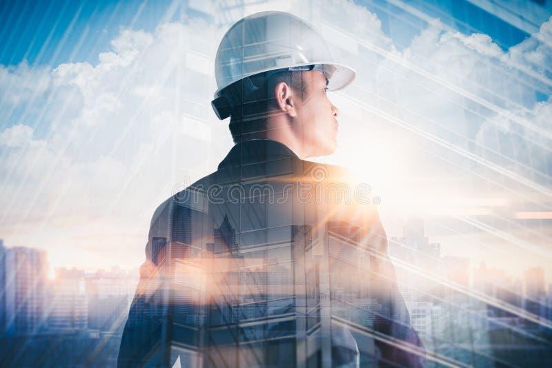 站立在日出期间的工程师的两次曝光图象躺在与都市风景图象 工程学,c的概念 库存照片