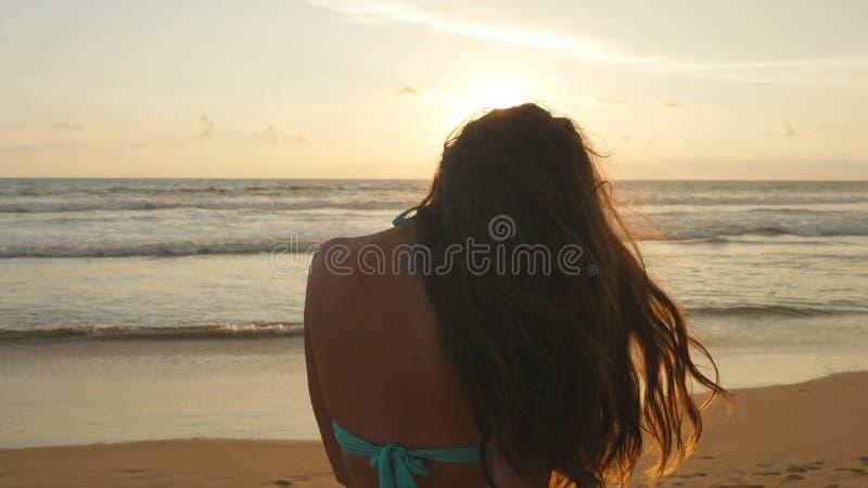 站立在日落的海附近的比基尼泳装的美丽的少妇 有摆在海洋的长的头发的可爱的性感的女孩 免版税库存图片