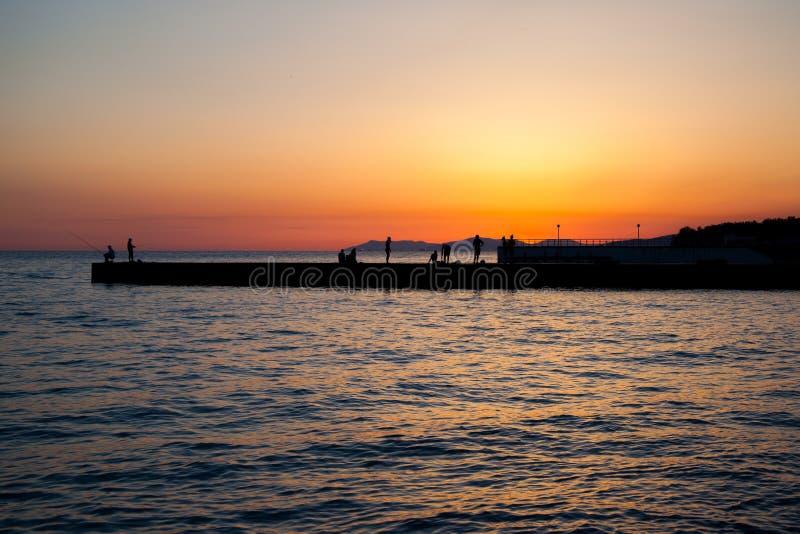 站立在日落的码头的人们 免版税库存图片