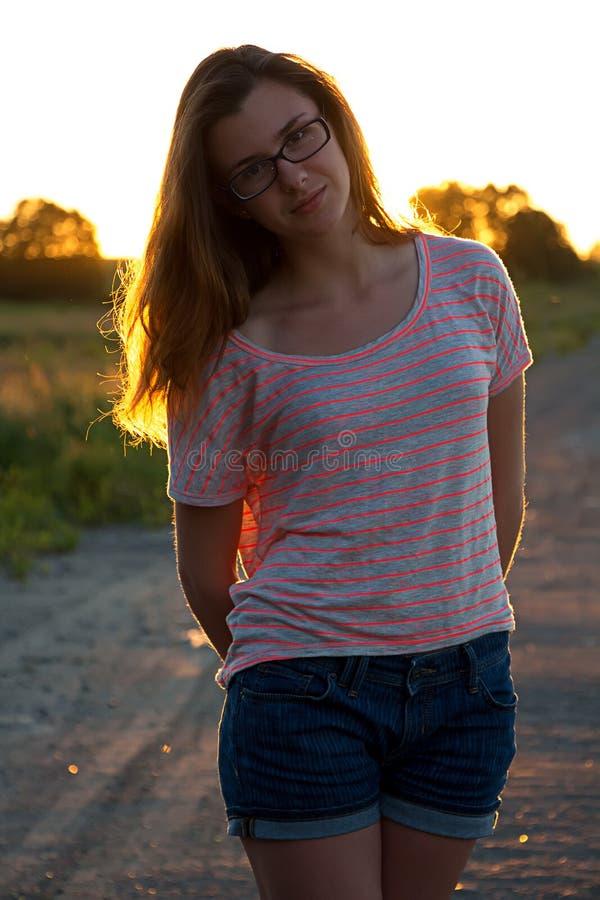 站立在日落的美丽的少年女孩 免版税库存图片