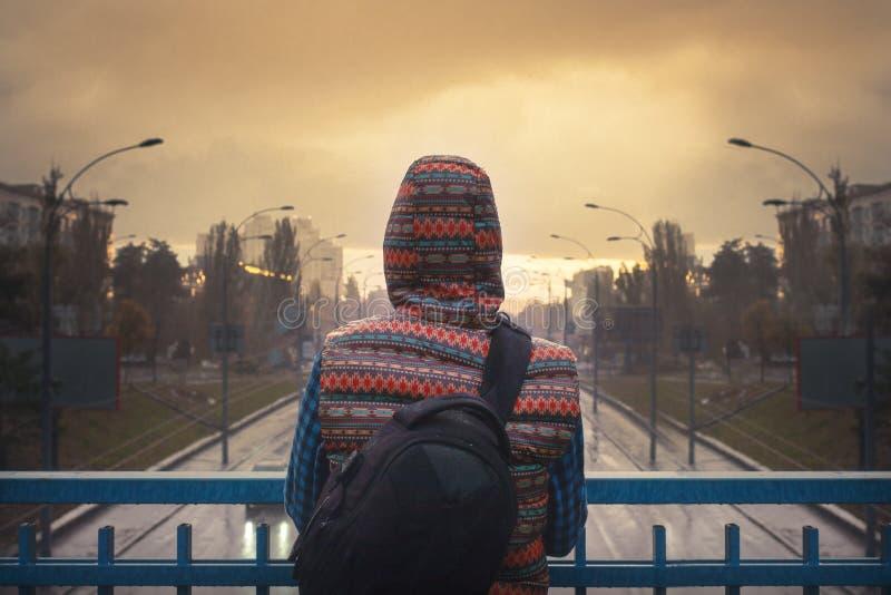 站立在日落的铁桥梁的少妇 库存图片
