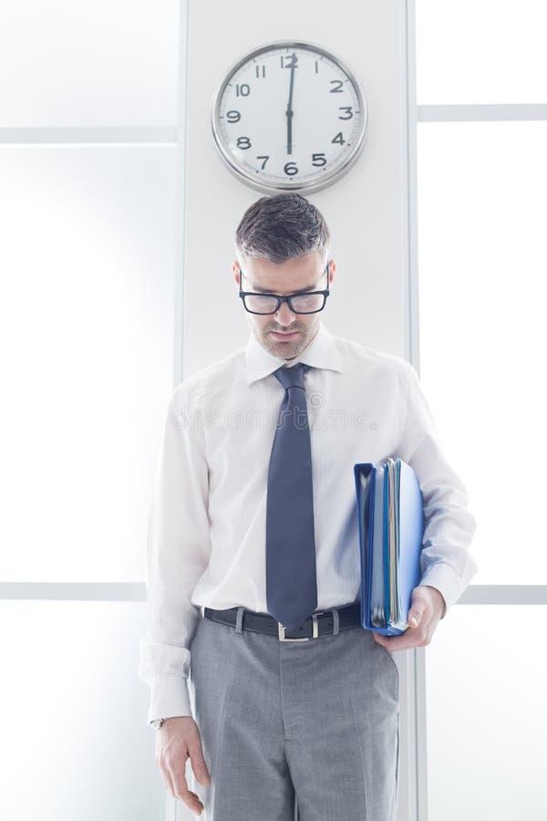 站立在时钟下的沮丧的商人 免版税图库摄影