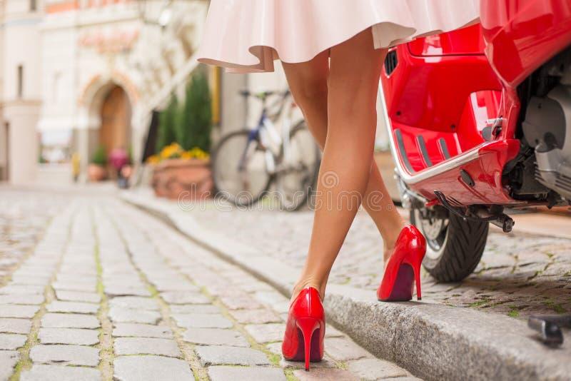 站立在时髦的红色moto滑行车旁边的高跟鞋的妇女 库存照片