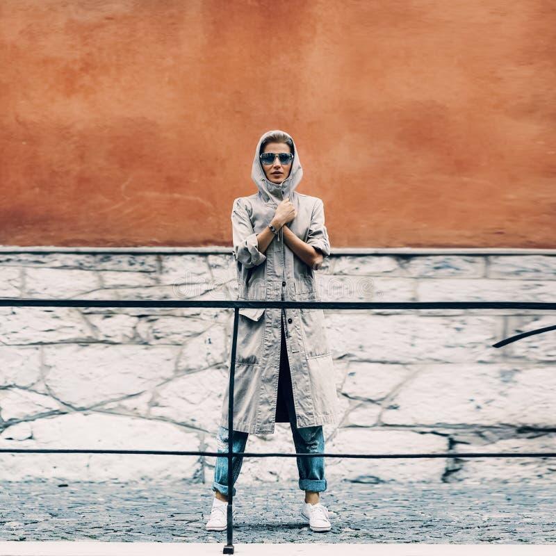 站立在明亮的墙壁的城市街道上的女孩 库存图片