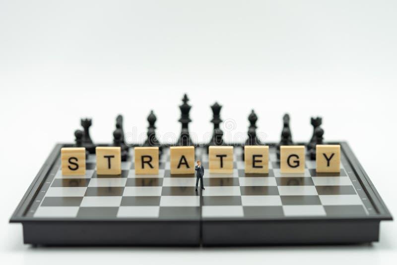 站立在有一个棋子的一杆棋枰的微型商人在后面 作为背景与拷贝空间的企业概念 库存图片