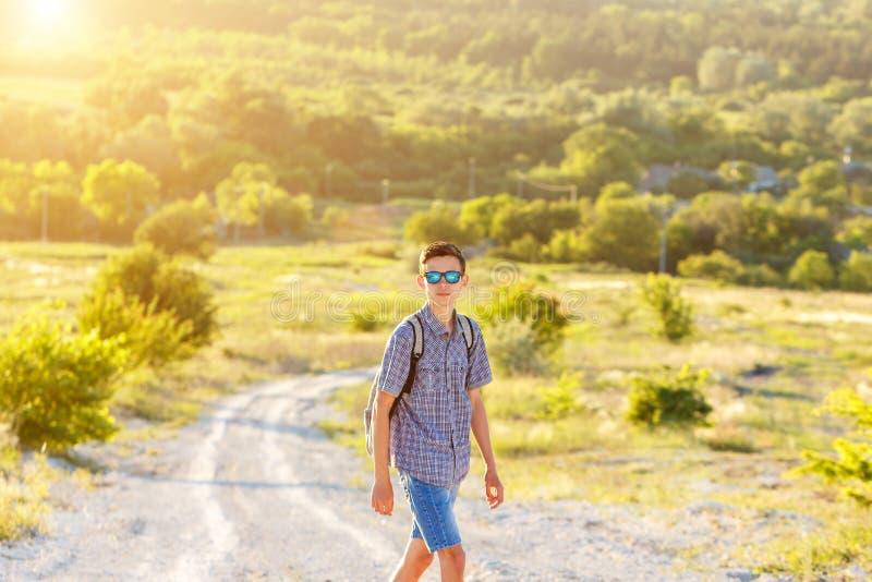 一个人背包旅行_站立在有一个背包的一条土路的旅游人在旅行和旅游业的日落概念的玻璃