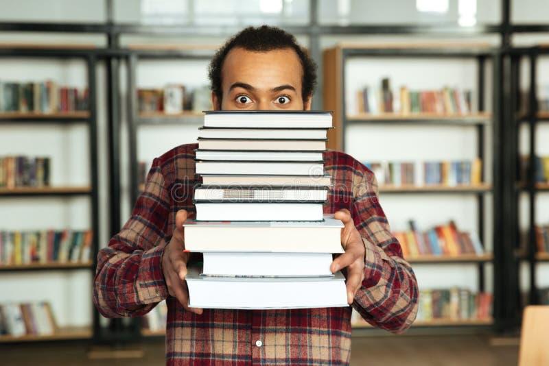 站立在有书的图书馆里的震惊非洲人学生 库存图片