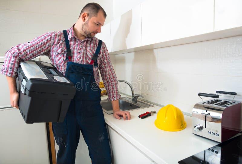 站立在有他的工具箱的厨房里的英俊的杂物工 免版税库存照片