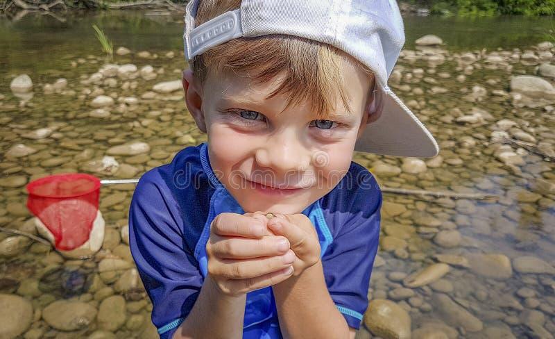 站立在有他的青蛙的河的骄傲的年轻男孩 库存图片