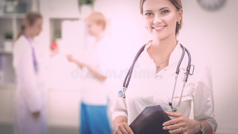 站立在有医疗听诊器的医院的少妇医生 图库摄影