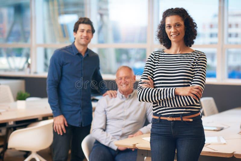 站立在有同事的一个办公室的确信的女实业家在她后 免版税图库摄影