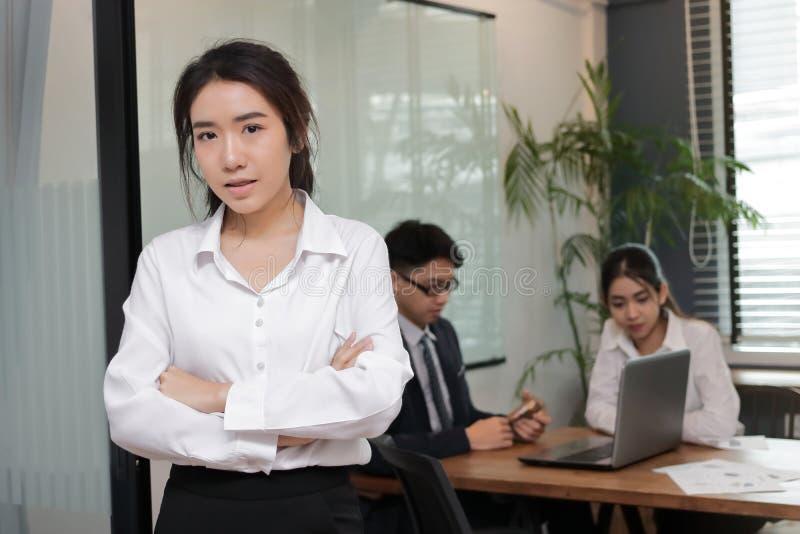 站立在有同事的办公室的确信的年轻亚裔女商人画象在会议室背景中 免版税图库摄影