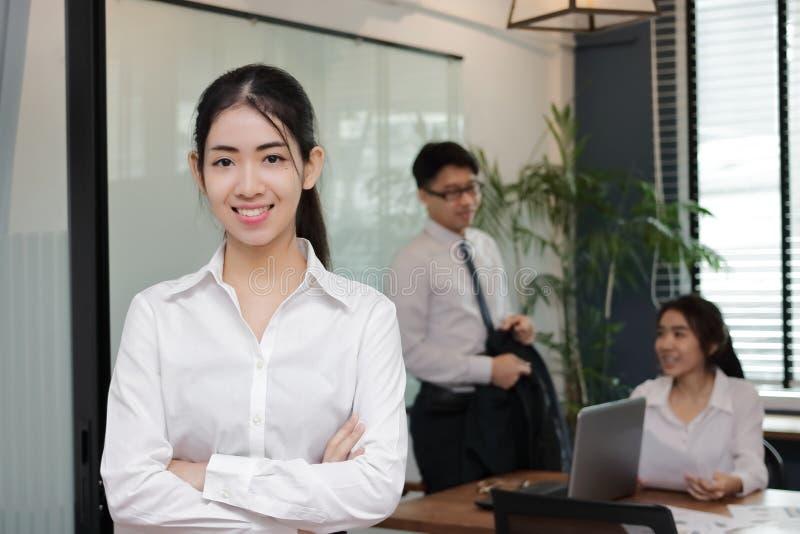 站立在有同事的办公室的确信的年轻亚裔女商人画象在会议室背景中 库存图片