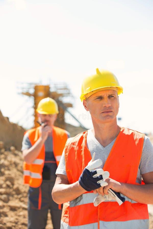 站立在有同事的建造场所的男性工作者在背景中 库存照片