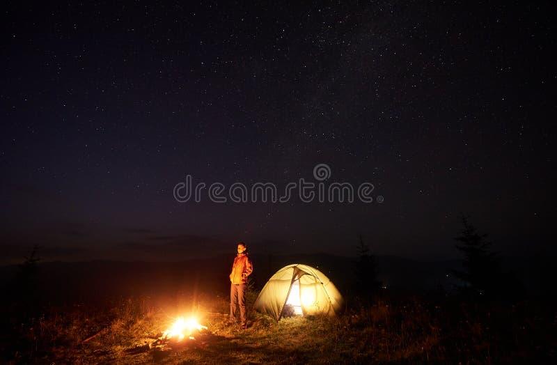 站立在有启发性帐篷附近的年轻女性游人,野营在山在晚上在满天星斗的天空下 免版税图库摄影