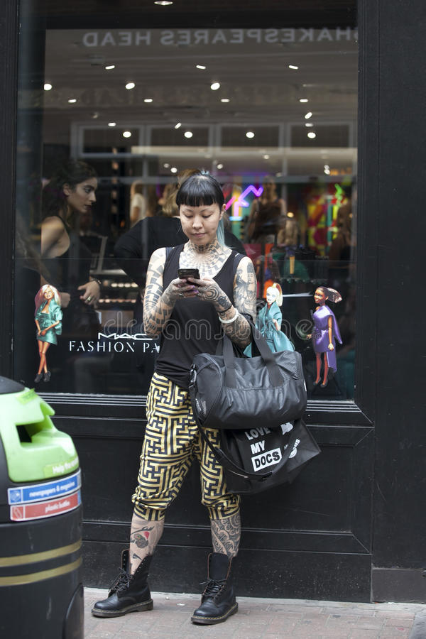 站立在有她的智能手机的商店附近的时兴的女孩 库存图片