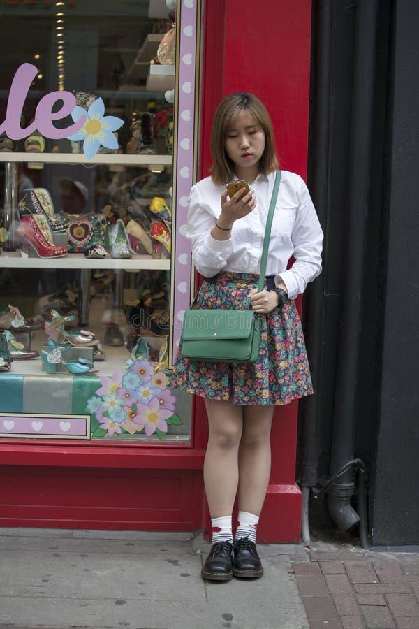 站立在有她的智能手机的商店附近的时兴的女孩 免版税库存图片