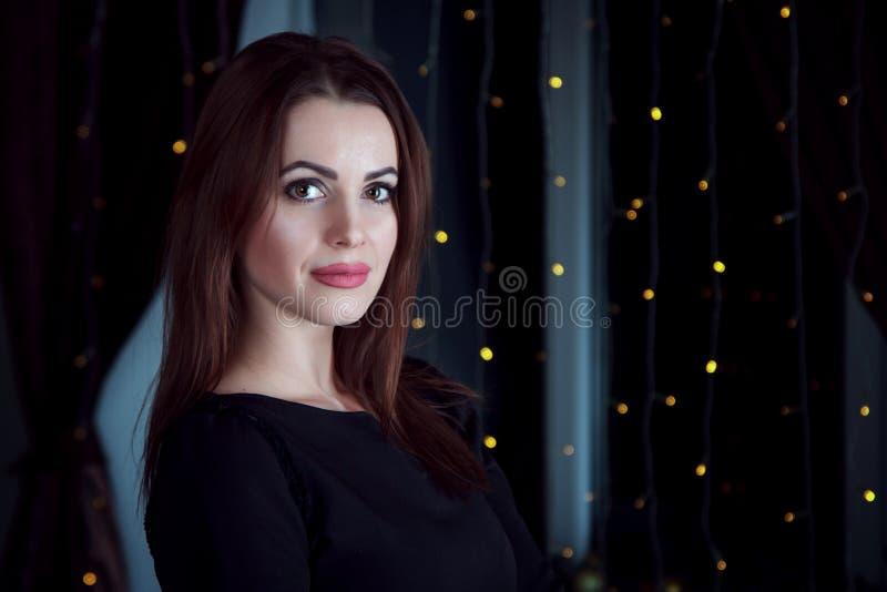 站立在有彩色小灯的一间屋子里的美丽的年轻深色的妇女画象在窗口 图库摄影