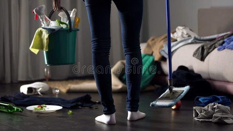 站立在有拖把和洗涤的桶的杂乱旅馆客房的震惊清洁女工 免版税库存图片