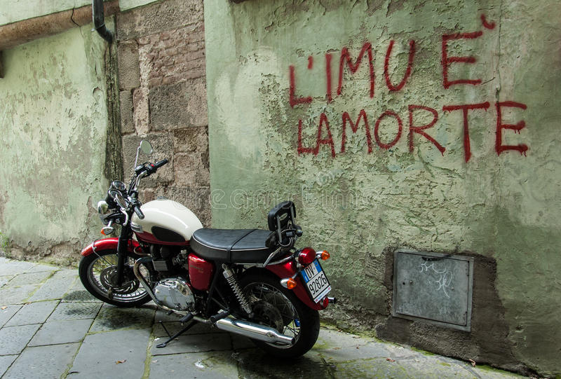 站立在有文字的墙壁前面的老摩托车 库存图片