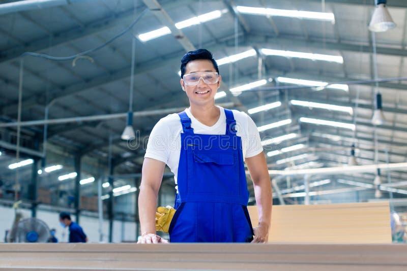 站立在有木委员会的车间的亚裔木匠 免版税库存图片