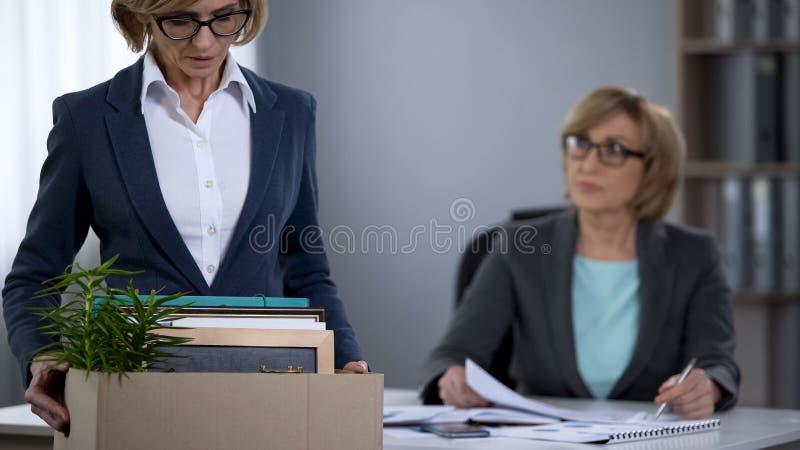 站立在有材料的,失业问题上司办公室的被遣散的女工 免版税库存照片
