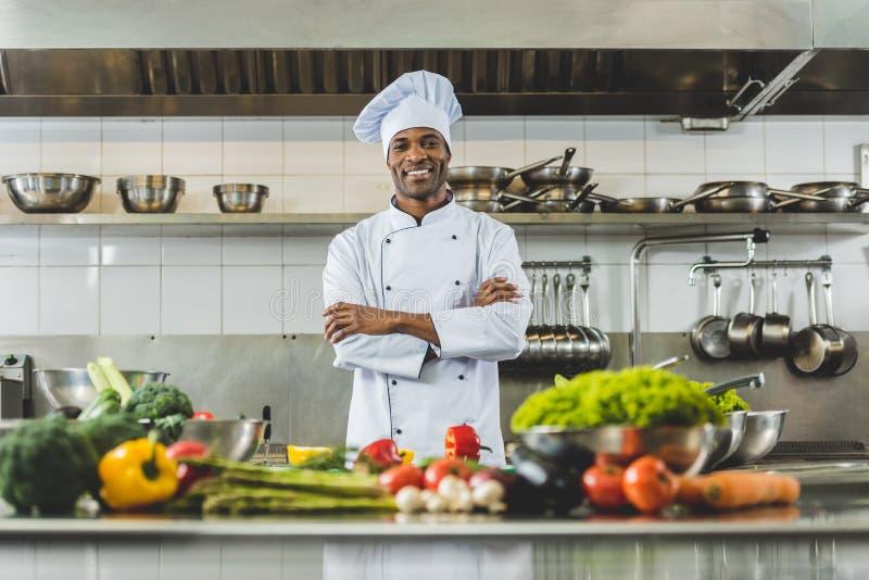 站立在有横渡的胳膊和看的餐馆厨房的英俊的非裔美国人的厨师 库存图片