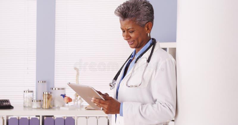 站立在有片剂的办公室的愉快的黑人资深医生 图库摄影