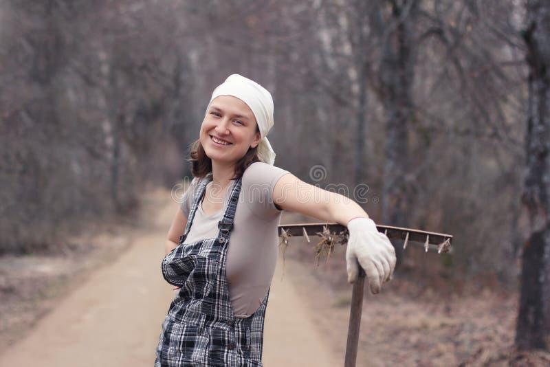 站立在有犁耙的农村路的花匠或农夫妇女 疲乏 图库摄影