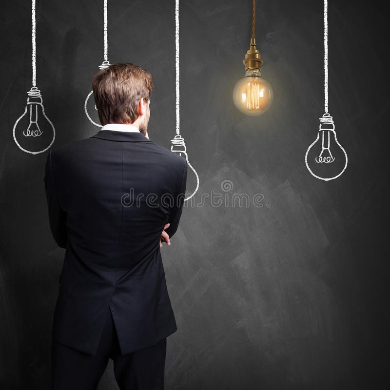站立在有电灯泡的一个黑板前面的成功的商人,象征有想法 免版税图库摄影