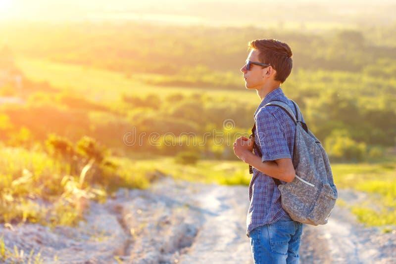 站立在有看太阳的背包的路的一个年轻人 免版税图库摄影