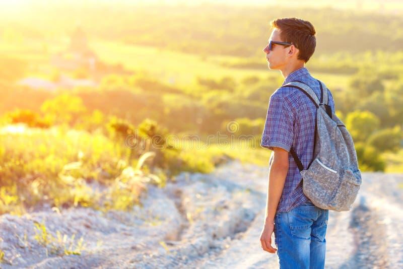 站立在有看太阳的背包的路的一个年轻人 库存图片